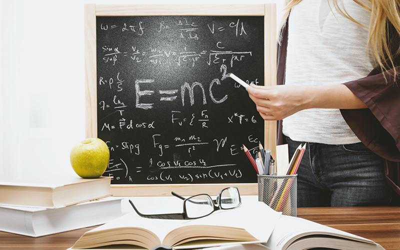 Girl holding chalk in front of a chalkboard with physics equations, behind a pile of books and pencils.