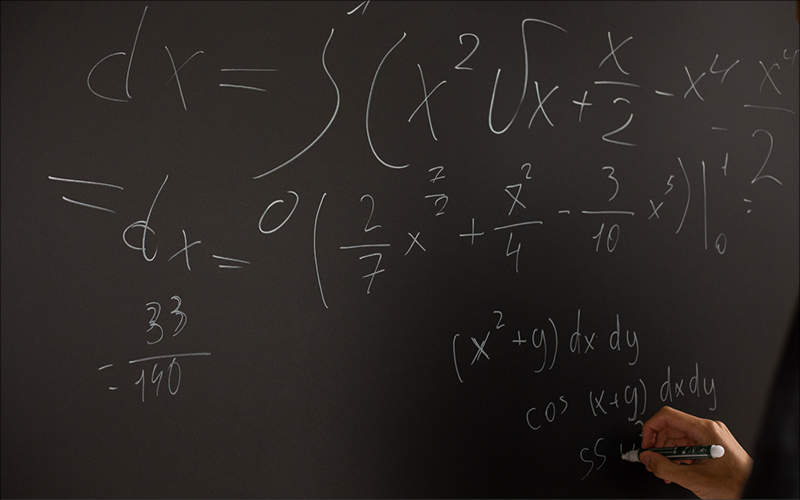 Person writing complex math equations on a chalkboard