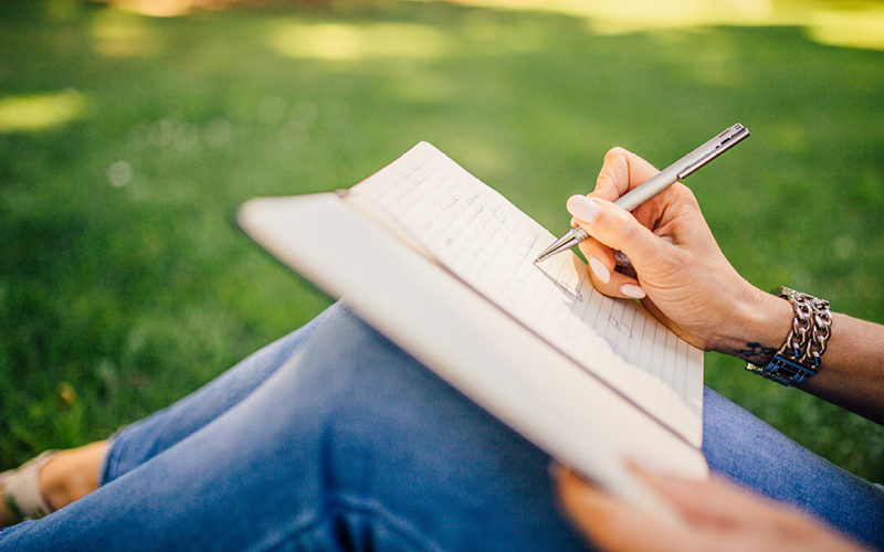 Person sitting in grass, writing with a pen in a notebook